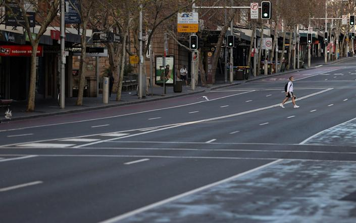 A lone man wearing a protective face mask crosses an empty street during a lockdown to curb the spread of a coronavirus disease (COVID-19) outbreak in Sydney, Australia, July 22, 2021. - Reuters