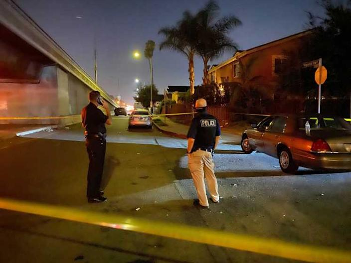 Crime tape surrounds the scene where a 17-year-old boy was fatally shot in South L.A. Saturday night, as Los Angeles Police officials work the scene.
