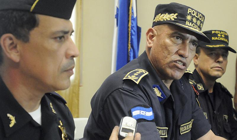 """In this July 3, 2012 photo, Honduras Police Chief, Gen. Juan Carlos Bonilla, center, speaks to the press during a news conference in Tegucigalpa, Honduras. The five-star general was accused a decade ago of running deaths squads and today oversees a department suspected of beating, killing and """"disappearing"""" its detainees. He also is the top cop in the country that serves as a way station for most South American cocaine bound for the United States and beyond. Bonilla is also the U.S. government's go-to man in Honduras for the war on drug trafficking. (AP Photo/Fernando Antonio)"""