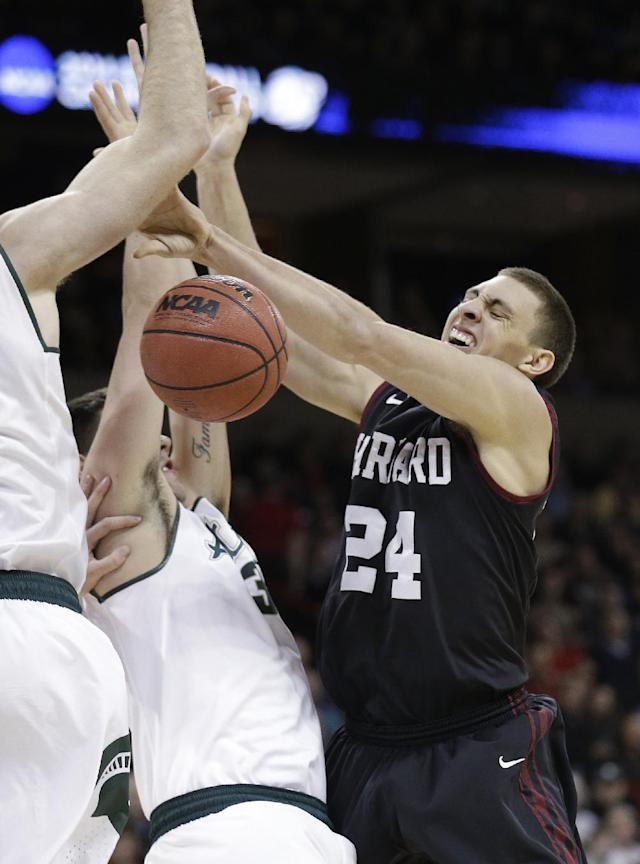Harvard's Jonah Travis (24) loses the ball as he runs into Michigan State's Kenny Kaminski in the first half during the third round of the NCAA men's college basketball tournament in Spokane, Wash., Saturday, March 22, 2014. (AP Photo/Elaine Thompson)