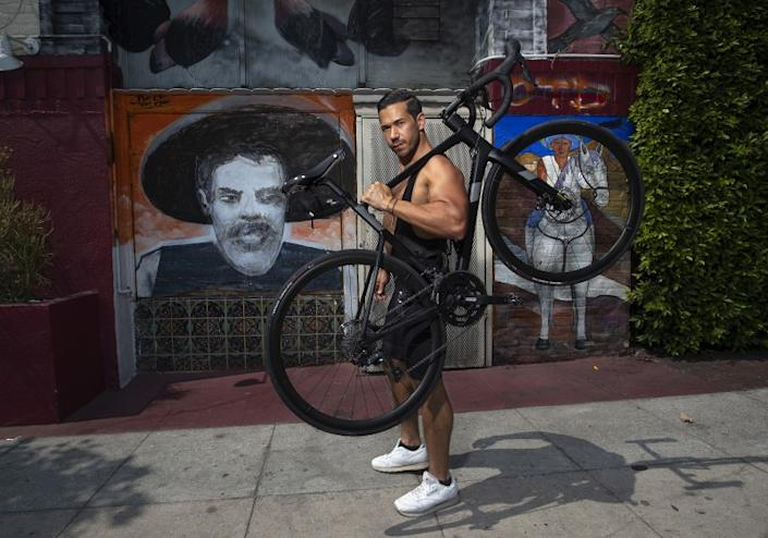 """Seth Gottesdiener holds the Cannondale bike that he plans to ride from Los Angeles to Washington. Gottesdiener wants to raise awareness to issues of racial and social injustice in America. <span class=""""copyright"""">(Mel Melcon / Los Angeles Times)</span>"""