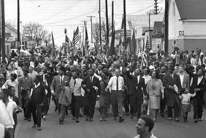 """FILE - In this March 21, 1965 file photo, Dr. Martin Luther King, foreground row, fifth from right, waves as marchers stream across the Alabama River on the first of a five day, 50-mile march to the state capitol at Montgomery, Ala. The annual celebration of the Martin Luther King Jr. holiday in his hometown in Atlanta is calling for renewed dedication to nonviolence following a turbulent year. The slain civil rights leader's daughter, the Rev. Bernice King, said in an online church service Monday, Jan. 18, 2021, that physical violence and hateful speech are """"out of control"""" in the aftermath of a divisive election followed by a deadly siege on the U.S. Capitol in Washington by supporters of President Donald Trump. (AP Photo/File)"""