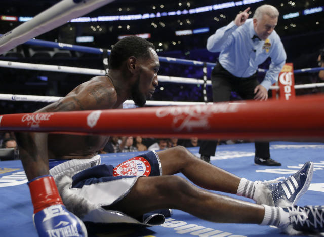 Robert Easter Jr., left, sits after being knocked down by Mikey Garcia, as referee Jack Reiss counts during the third round of the WBC and IBF lightweight title bout in Los Angeles, Saturday, July 28, 2018. Garcia won by unanimous decision. (AP Photo/Alex Gallardo)