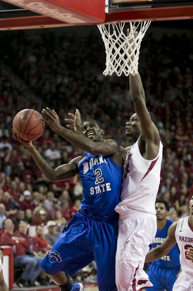 Indiana State guard Dawon Cummings (12) drives to the basket against Arkansas forward Moses Kingsley (33) during the first half of an opening round National Invitational Tournament NCAA college basketball game in Fayetteville, Ark., Tuesday, March 18, 2014. (AP Photo/Gareth Patterson)