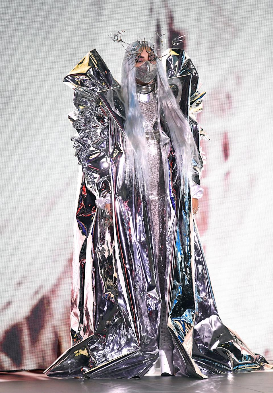 """For once, Gaga didn't do a complete outfit change for this look. Instead, she kept on her Valentino catsuit, and just swapped out her feathered cape for a Candace Cuoco ice-like jacket and an avant-garde headpiece that could also double as a social distancing tool.<br><br><em>Lady Gaga is wearing a Candace Cuoco jacket, a Valentino catsuit, a Manuel Albarran choker and bra, Lance Victor Moore face armor, and Pleaser shoes.</em><br><br><br><br><span class=""""copyright"""">Photo: Kevin Winter/Getty Images.</span>"""