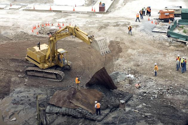 NEW YORK - JUNE 12:  An excavator moves protective mats into position over the hole where test blasts were placed and later fired in preparation for the footings of the Freedom Tower at the World Trade Center site June 12, 2006 in New York City. The blasts, which were buried more than 85 feet below street level, resonated about 15 seconds and were faintly heard by pedestrians along Vesey Street.  (Photo by Michael Brown/Getty Images)