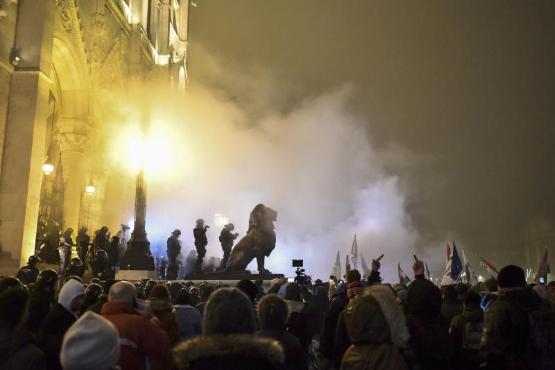 """Protesters demonstrate against the amendments to the labor code, dubbed """"slave law"""" by oppositional forces, at the parliament building in Budapest, Hungary, Dec. 13, 2018. The rally, which was announced by the Free University and Students Trade Union student groups, started peacefully but police later responded to aggressive protestors with teargas. (Marton Monus/MTI via AP)"""