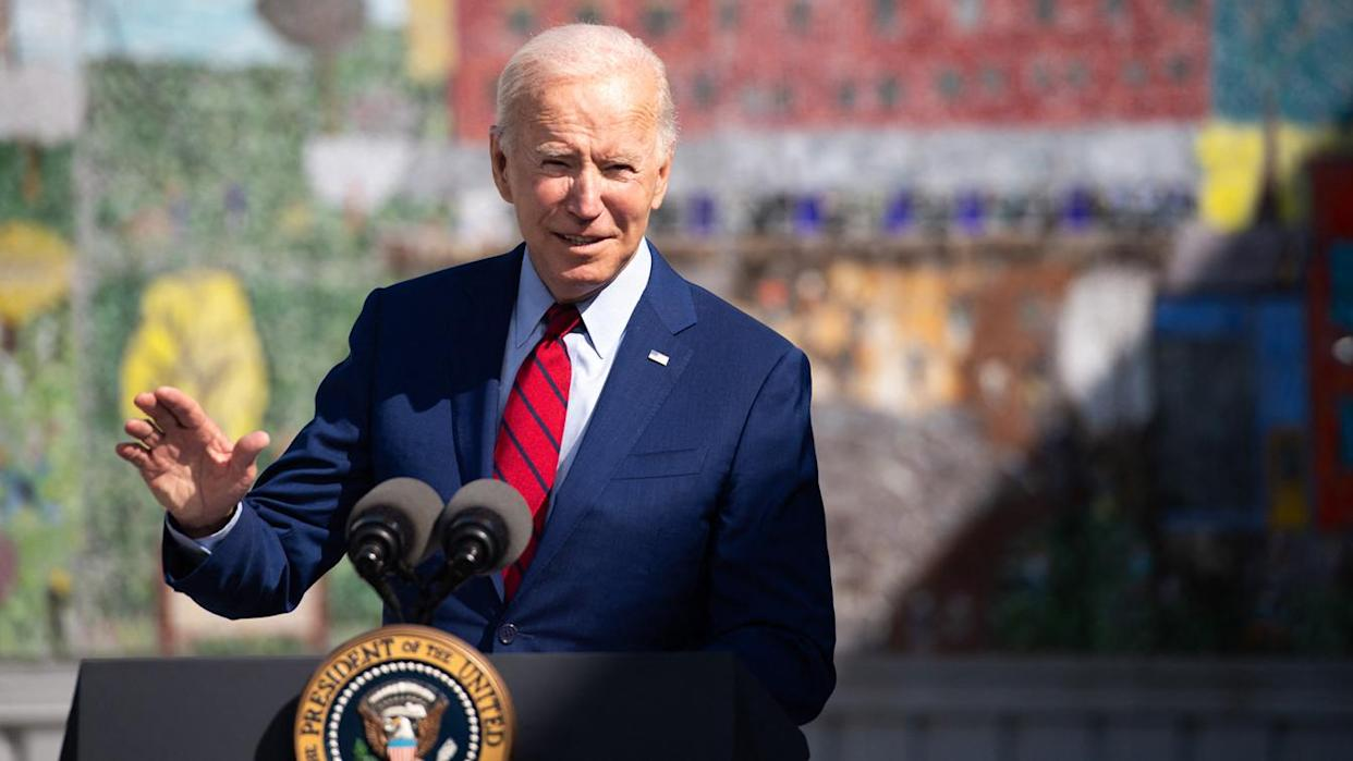 President Biden gestures with his hand while standing at a podium with two microphones and a presidential seal.