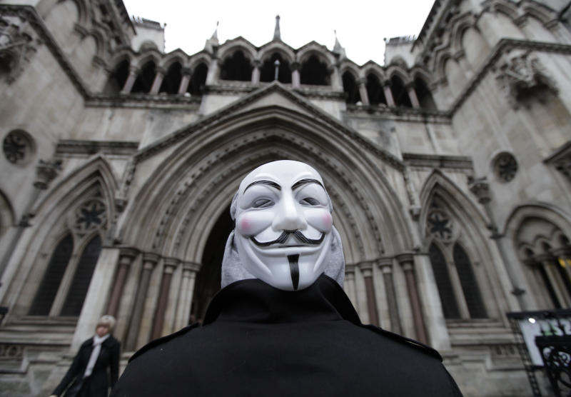 A protester wearing a Guy Fawkes mask stands outside the High Court in London following news that the City of London Corporation has won its legal bid to evict anti-capitalist protesters from outside St. Paul's Cathedral, Wednesday, Jan. 18, 2011.  The Occupy London protest camp that has sprawled outside the city's 300-year old St. Paul's Cathedral for some three months must be removed, a British judge ruled Wednesday. (AP Photo/Lefteris Pitarakis)