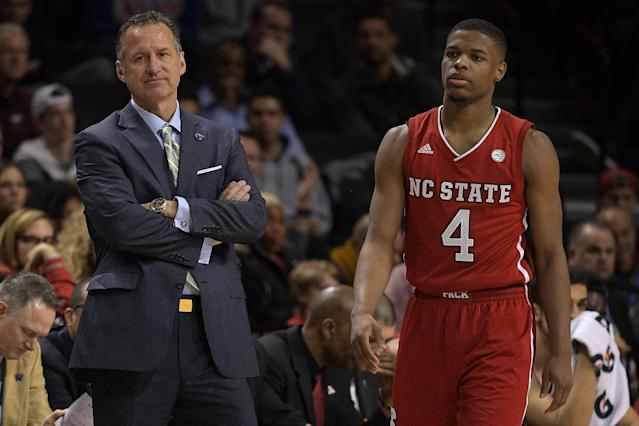 "Former NC State coach Mark Gottfried (L) watches action while former Wolfpack player <a class=""link rapid-noclick-resp"" href=""/nba/players/5822/"" data-ylk=""slk:Dennis Smith Jr"">Dennis Smith Jr</a>. walks by during an ACC tournament game in 2017. (Getty)"