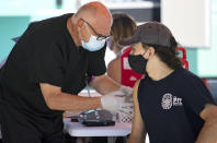 A person getting a Johnson & Johnson vaccine by a health care worker at the one-time pop-up vaccination site located 16th Street beach on the sand on Sunday, May 2, 2021 in Miami Beach. The one-time vaccination site made possible by Miami Beach Commissioner David Richardson and the Florida Division of Emergency Management will administer up to 250 Johnson & Johnson vaccines. (David Santiago/Miami Herald via AP)