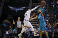 Charlotte Hornets forward Cody Martin, right, breaks up a pass by Denver Nuggets guard Jamal Murray during the first half of an NBA basketball game in Charlotte, N.C., Thursday, March 5, 2020. (AP Photo/Nell Redmond)