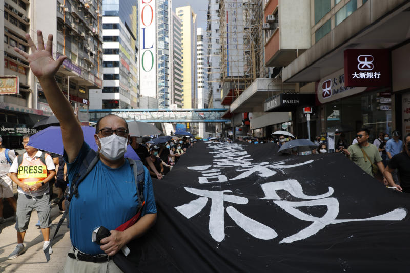 A protester wears a mask and holds up his hand to represent the five demands as he walks with a protest slogan banner in Hong Kong on Saturday, Oct. 5, 2019. All subway and trains services are closed in Hong Kong after another night of rampaging violence that a new ban on face masks failed to quell. (AP Photo/Vincent Thian)