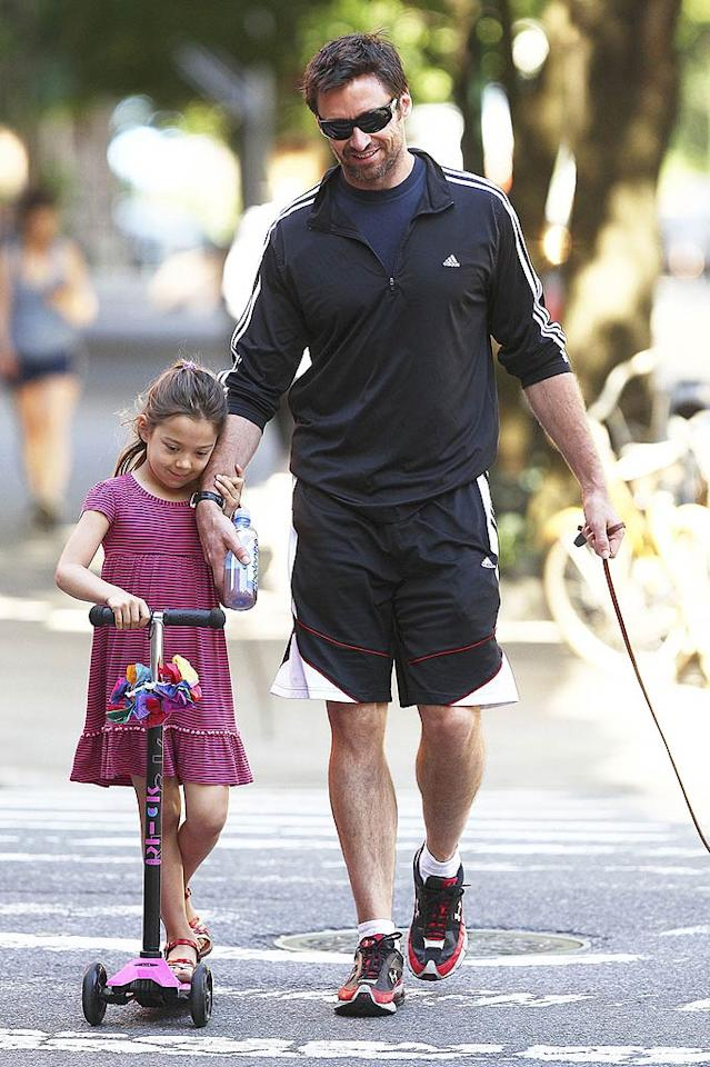 """Riding a scooter is a breeze when you can hang on to your dad's arm during the ride! Hugh Jackman accompanied 5-year-old daughter Ava to school in New York while walking the family dog at the same time. Wagner Az/<a href=""""http://www.pacificcoastnews.com/"""" target=""""new"""">PacificCoastNews.com</a> - June 1, 2011"""
