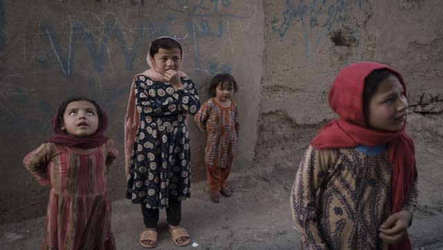 Afghan girls look up and listen as a neighbour describes when two men fell from a US Air Force C-17 and landed on the rooftop of his house in Kabul on August 16. AP