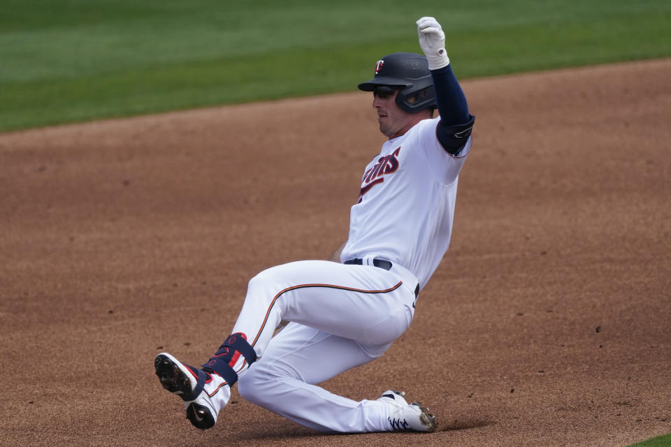 Minnesota Twins left fielder Brent Rooker (50) slides into second base with a double in the third inning of a spring training baseball game against the Boston Red Sox Sunday, March 14, 2021, in Fort Myers, Fla.. (AP Photo/John Bazemore)
