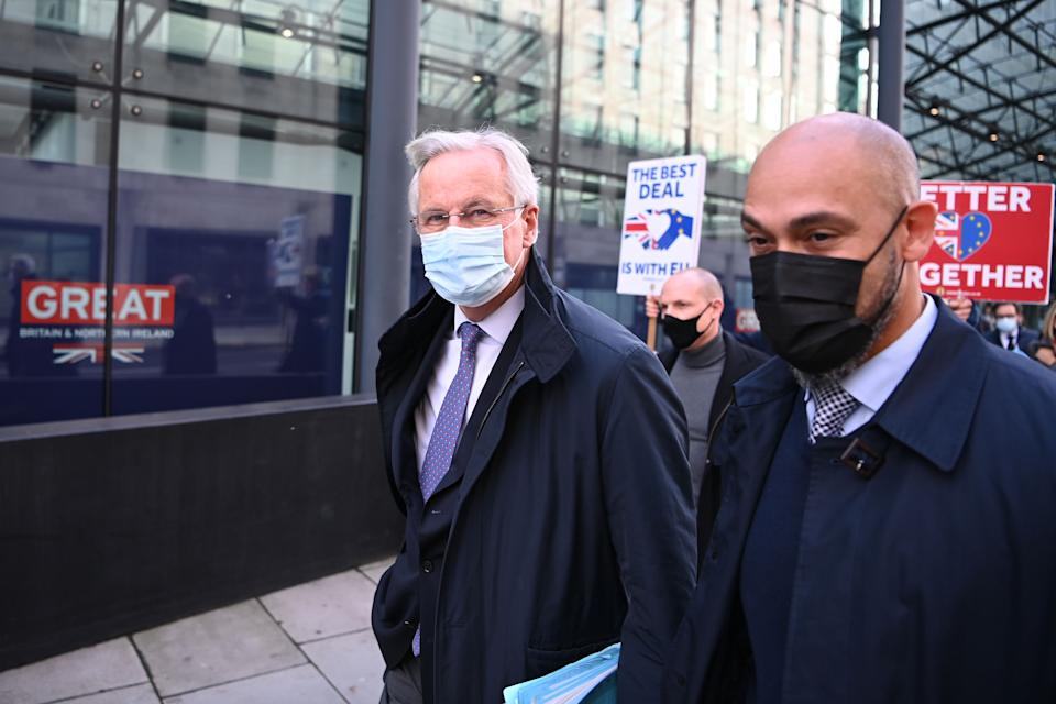 EU chief negotiator Michel Barnier (L) wearing a face mask because of the novel coronavirus pandemic, is followed down a street by Anti-Brexit activists as talks continue between the EU and the UK in London on November 13, 2020. - The European Union and Britain said major divergences remain but that post-Brexit negotiations would continue this week to clinch a trade deal in the scant time left. (Photo by DANIEL LEAL-OLIVAS / AFP) (Photo by DANIEL LEAL-OLIVAS/AFP via Getty Images)