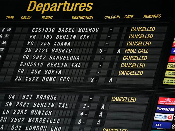 An airport departures board showing canceled flights.