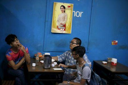 Men sit in a tea house under a calendar with a picture of Aung San Suu Kyi in Yangon