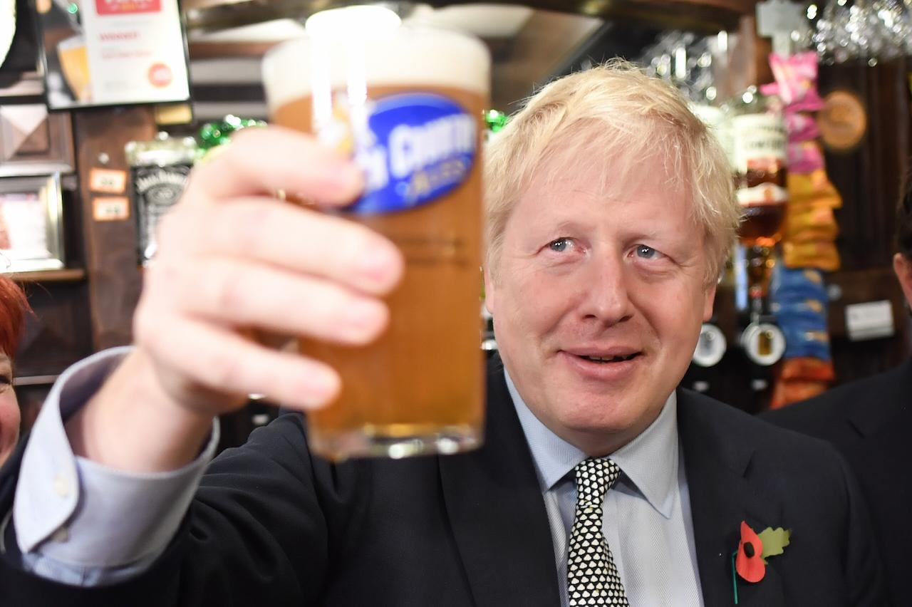 Prime minister Boris Johnson raises a pint as he meets with military veterans at the Lych Gate Tavern in Wolverhampton on Monday (Picture: PA)