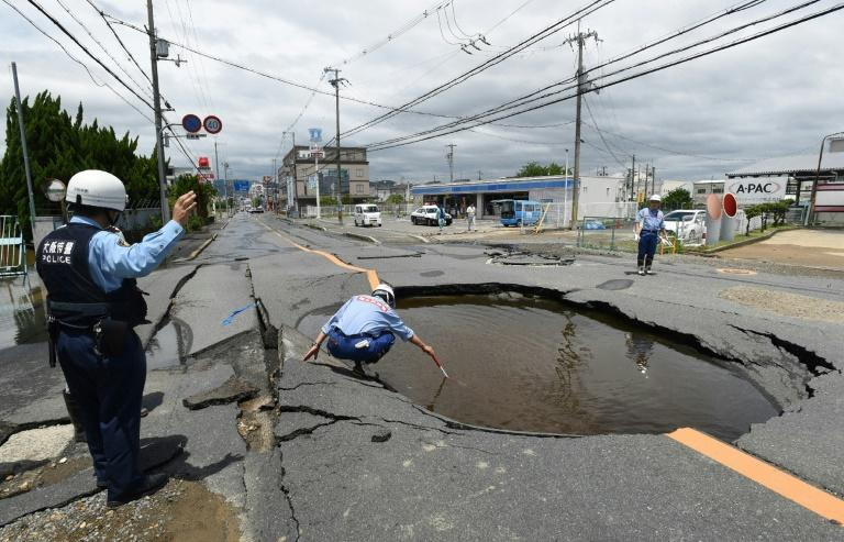 Police check a collapsed road in Takatsuki, north of Osaka prefecture