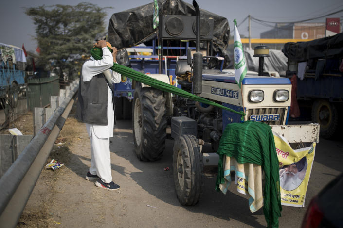 Jagir Singh, 71, ties his turban before joining fellow farmers for a protest against new farm laws, at the Delhi-Haryana state border, India, Tuesday, Dec. 1, 2020. The farmers have laid a siege of sorts on the highway, sleeping inside the trailers or under the trucks at night. During the day, they sit huddled in groups at the backs of the vehicles, surrounded by mounds of rice, lentils and vegetables. They say they are not going to leave the place until their demands are met. (AP Photo/Altaf Qadri)
