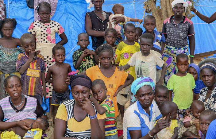 Women and children sit outside their tents in a makeshift site for displaced people in Kongoussi, Burkina Faso, Thursday, June 4, 2020. Jihadist violence has dramatically escalated in Burkina Faso in recent years. The country's military has struggled to contain the violence. (AP Photo/Sam Mednick)