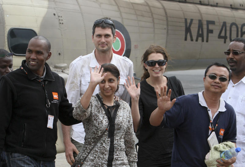 EDS NOTE: RECROP of NAI104. Released aid workers Qurat-Ul-Ain Sadazai, 38, a Canadian citizen of Pakistani origin, center-left, Glenn Costes of the Philippines, 40, 2nd right, Steven Dennis of Canada, 37, above-center-left, and Astrid Sehl of Norway, 33, center-right, arrive by Kenyan military helicopter at Wilson airport in Nairobi, Kenya Monday, July 2, 2012. A pro-government Somali militia group said Monday that it rescued the four aid workers kidnapped by gunmen from a refugee camp in Kenya last week. (AP Photo/Sayyid Azim)