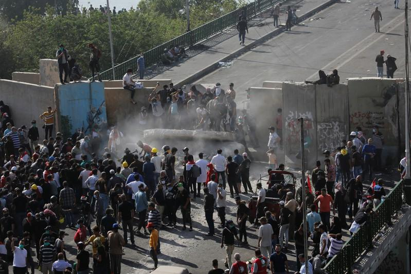 Iraqi demonstrators smash concrete walls at Sinak Bridge during the ongoing anti-government protests, in Baghdad