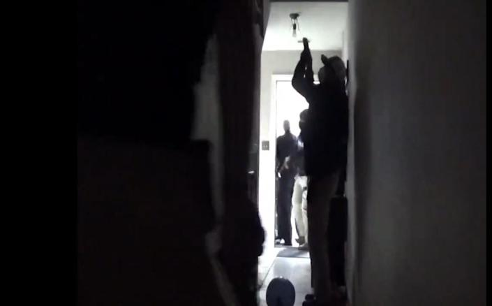 At least four armed officers are shown in the doorway and hall of Rebekah Jones' home.