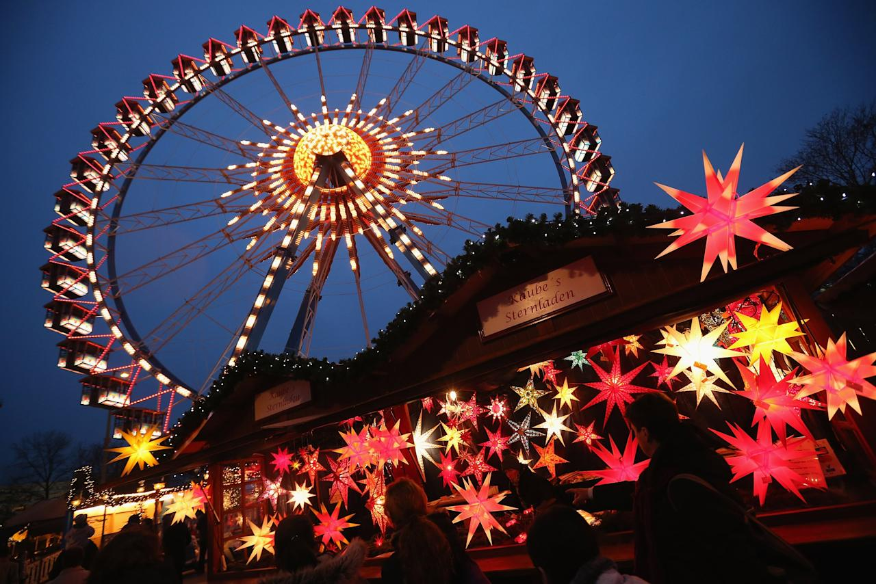 BERLIN, GERMANY - NOVEMBER 28:  Visitors walk past a stall selling illuminated Christmas stars at the annual Christmas market at Alexanderplatz two days after the market opened on November 28, 2012 in Berlin, Germany. Christmas markets, with their stalls selling mulled wine (Gluehwein), Christmas tree decorations and other delights, are an integral part of German Christmas tradition, and many of them are opening across Germany this week.  (Photo by Sean Gallup/Getty Images)