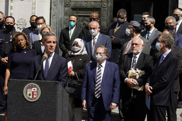 Los Angeles Mayor Eric Garcetti, at podium, speaks in front of civic and faith leaders outside City Hall, Thursday, May 20, 2021, in Los Angeles. Faith and community leaders in Los Angeles called for peace, tolerance and unity in the wake of violence in the city that is being investigated as potential hate crimes. (AP Photo/Marcio Jose Sanchez)