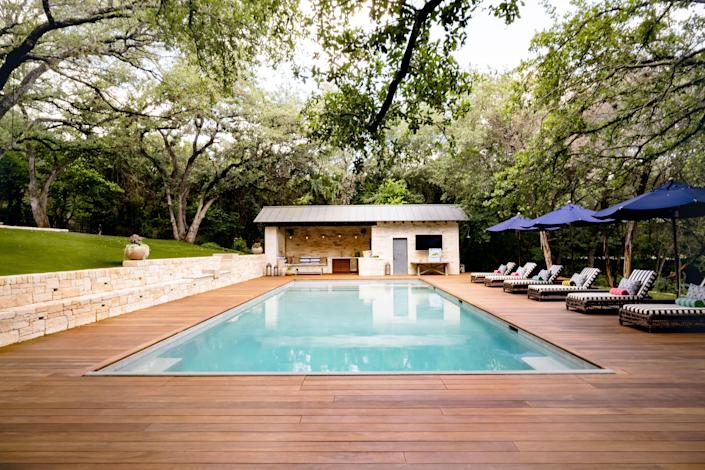 The serene pool area. Janus et Cie chaise longues with outdoor throw pillows from Perennials and umbrellas from Santa Barbara Designs line the deck. The cushions and pillows in the cabana sectional are from Sunbrella Fabrics.