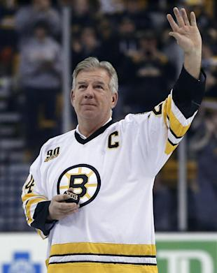 Former Boston Bruins player Terry O'Reilly waves to the crowd after a ceremonial puck drop prior to the Bruins' NHL hockey game against the Calgary Flames in Boston, Tuesday, Dec. 17, 2013. (AP Photo/Elise Amendola)