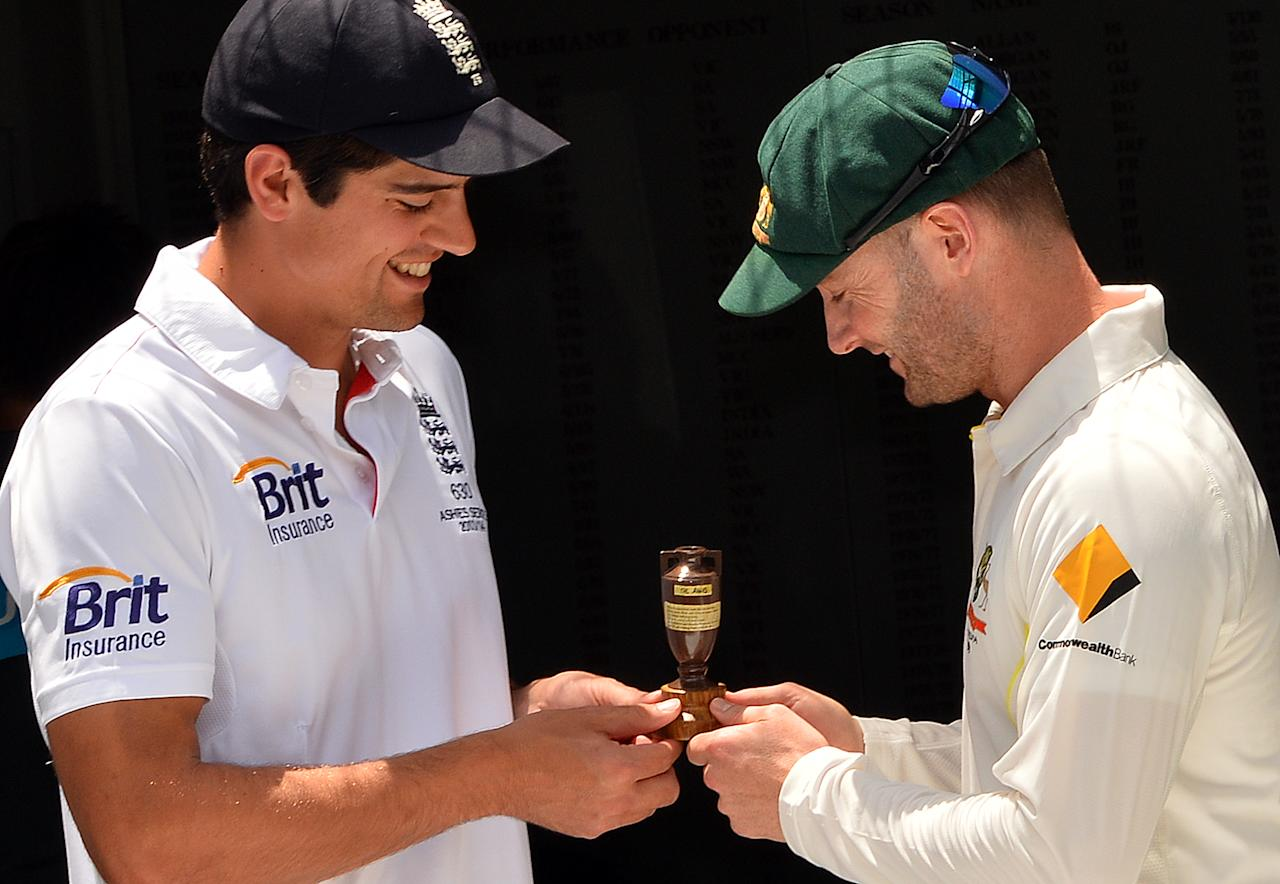 England Captain Alistair Cook (L) and Australian Captain Michael Clarke pose with the Ashes Urn at the Gabba in Brisbane on November 20, 2013, on the eve of the first Ashes cricket test match between England and Australia.   IMAGE RESTRICTED TO EDITORIAL USE - STRICTLY NO COMMERCIAL USE AFP PHOTO / Saeed KHAN        (Photo credit should read SAEED KHAN/AFP/Getty Images)