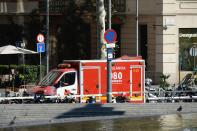<p>A policeman stands next to an ambulance after a van ploughed into the crowd, injuring several persons on the Rambla in Barcelona on August 17, 2017. (Josep Lago/AFP/Getty Images) </p>