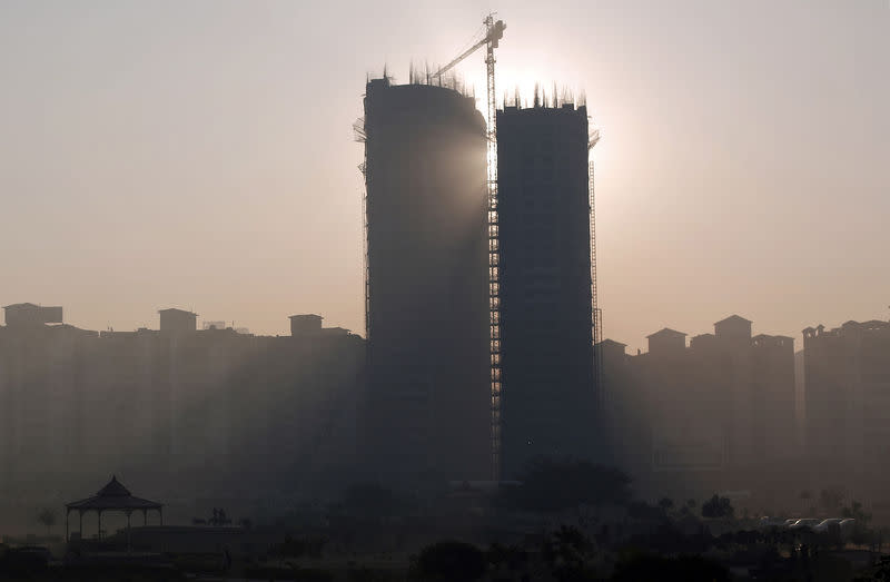 Sun rays beam through two under construction residential buildings in Noida