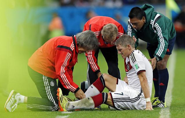Germany's Bastian Schweinsteiger receives treatment during the World Cup round of 16 soccer match between Germany and Algeria at the Estadio Beira-Rio in Porto Alegre, Brazil, Monday, June 30, 2014. (AP Photo/Frank Augstein)