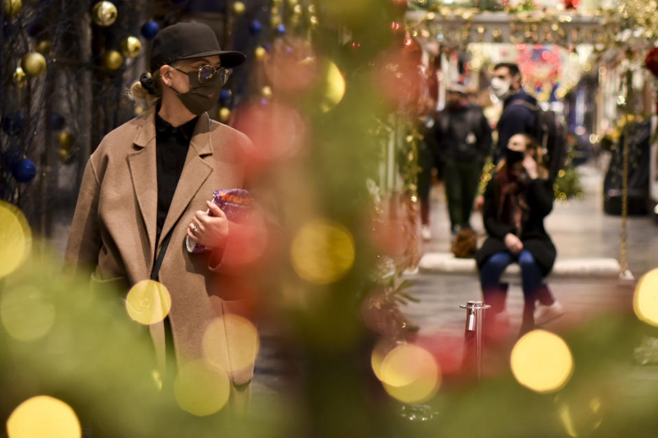 Shoppers wear a face masks at the Burlington Arcade in London, Tuesday, Dec. 22, 2020. Britain's government has imposed new restrictions across many regions, in an effort to restrict the spread of the new mutant coronavirus variant during Christmas festivities. (AP Photo/Alberto Pezzali)