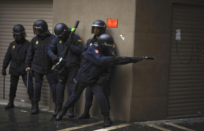 A riot policeman fires rubber bullets against demonstrators during a general strike in Pamplona, northern Spain on Thursday, May 30, 2013. People protested against the austerity measures and the economic crisis affecting the country with more than six million unemployed. Background is a fire lit by demonstrators. (AP Photo / Alvaro Barrientos)