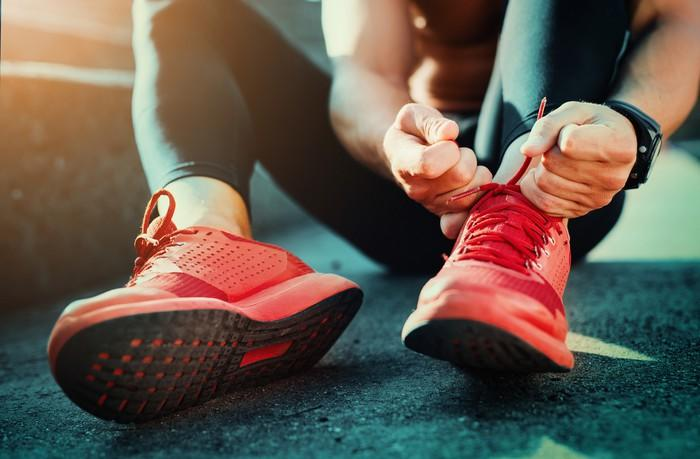 A jogger laces up before a run.