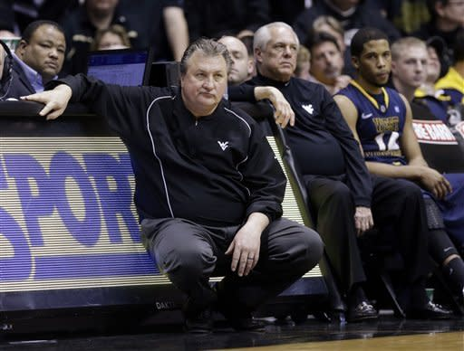 West Virginia head coach Bob Huggins, left, watches from the bench along with assistant Billy Hahn and guard Gary Browne, right, in the closing minutes of the second half of an NCAA college basketball game against Purdue in West Lafayette, Ind., Saturday, Jan. 19, 2013. Purdue defeated West Virginia 79-52. (AP Photo/Michael Conroy)