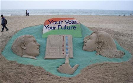 A visitor walks next to a sand sculpture on elections made by Indian sand artist Pattnaik at a beach at Puri