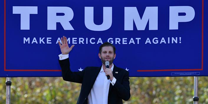 """Eric Trump speaking into a microphone and raising his other hand in front of a blue """"Trump: Make America Great Again"""" banner."""