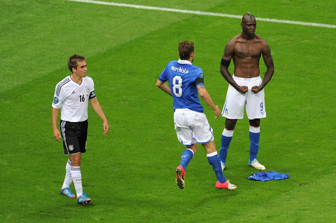 WARSAW, POLAND - JUNE 28:  Mario Balotelli (R) of Italy celebrates with team-mate Claudio Marchisio after scoring his team's second goal as Philipp Lahm of Germany shows his dejection during the UEFA EURO 2012 semi final match between Germany and Italy at the National Stadium on June 28, 2012 in Warsaw, Poland.  (Photo by Michael Regan/Getty Images)