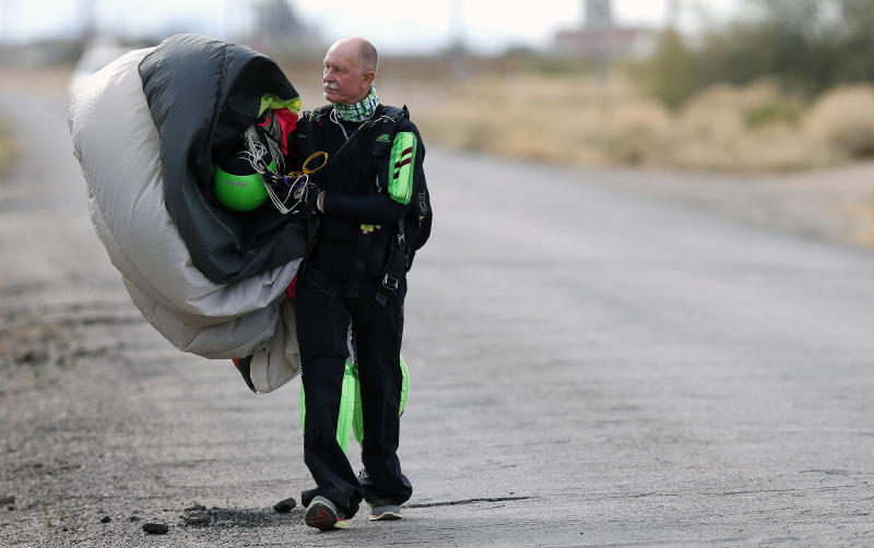 "Richard Luczak, of Poland, said he ""lost friends yesterday"" walks back to the airport after joining nearly 200 skydivers, from all over the world, to perform a group jump the day after two skydivers were killed after colliding in midair during a jump from Skydive Arizona at Eloy Municipal Airport, on Wednesday, Dec. 4, 2013, in Eloy, Ariz. (AP Photo/Ross D. Franklin)"