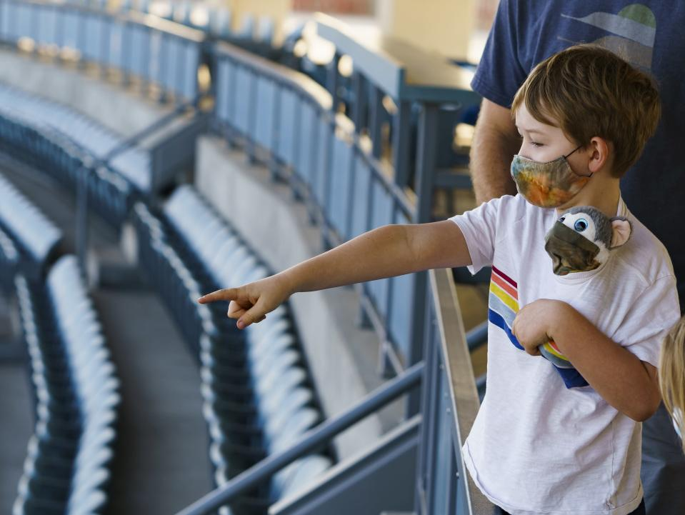 Voters Brandon Malmberg explains the rules of baseball to his son his son, Ashton Malmberg, 7, holding a masked stuffed toy, after his parents voted in-person on Election Day at Dodger Stadium in Los Angeles, Tuesday, Nov. 3, 2020. (AP Photo/Damian Dovarganes)