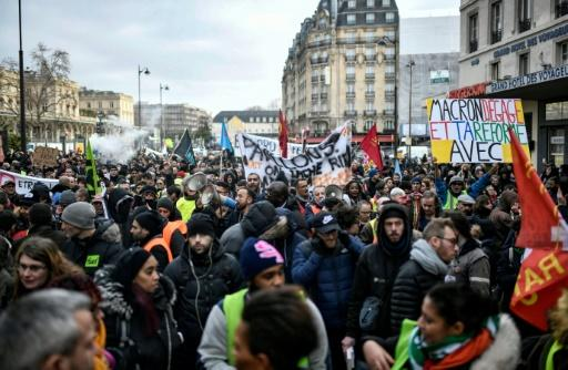 Protesters take part in a demonstration near Gare de l'Est train station in Paris on December 26