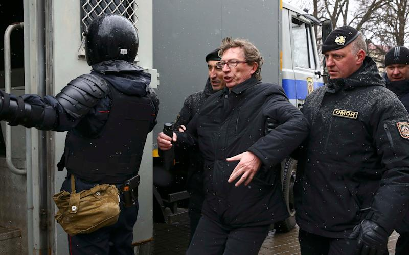 Members of police special forces detain a man during a gathering, denouncing the new tax on those not in full-time employment - AP