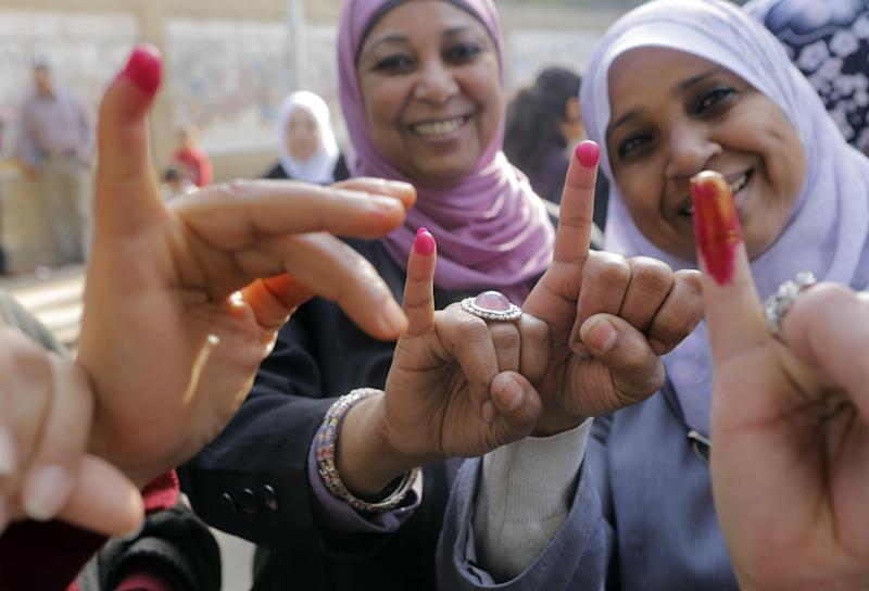 Egyptian women show their inked fingers after casting their votes at a polling station in Cairo, Tuesday, Jan. 14, 2014. Egyptians are voting on a draft for their country's new constitution that represents a key milestone in a military-backed roadmap put in place after President Mohammed Morsi was overthrown in a popularly backed coup last July. (AP Photo/Amr Nabil)
